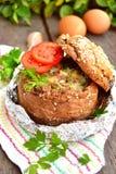 Ovos mexidos com bacon e vegetais dentro da bacia de pão fotografia de stock royalty free