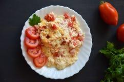 Ovos mexidos com os tomates na placa branca no fundo branco Fotos de Stock