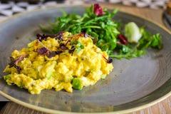 Ovos mexidos com salada do abacate e de foguete fotografia de stock