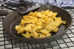 Ovos mexidos em uma bandeja do ferro fundido e em uma espátula Imagem de Stock