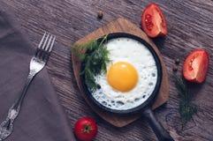 Ovos mexidos em uma frigideira com a erva-doce e os tomates na superfície de madeira, vista de cima de Fotos de Stock Royalty Free