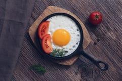 Ovos mexidos em uma frigideira do ferro fundido com tomates em uma tabela escura de madeira Fotografia de Stock