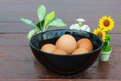 Ovos na bacia com as flores pequenas no fundo de madeira Imagem de Stock Royalty Free