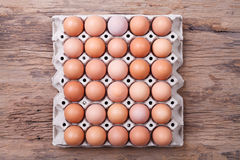 Ovos na bandeja de papel na tabela de madeira Imagens de Stock