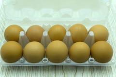 Ovos na caixa de cartão isolada no branco Fotos de Stock