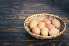 Ovos na cesta de bambu na tabela de madeira Fotografia de Stock Royalty Free