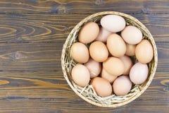 Ovos na cesta de bambu tabela de madeira na vista superior recolhida Imagens de Stock Royalty Free