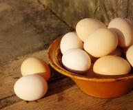 Ovos na placa cerâmica velha em uma superfície de madeira Fotos de Stock Royalty Free