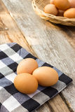 Ovos na toalha de mesa sobre a tabela de madeira Fotografia de Stock Royalty Free