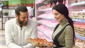 Ovos novos da compra da fam?lia na mercearia Movimento lento Retrato vídeos de arquivo