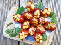 Ovos pintados na casca da cebola com ervas Ovos da p?scoa em uma placa em uma placa de madeira fotografia de stock