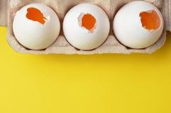 Ovos quebrados crus na caixa do ovo com fundo amarelo imagem de stock