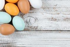 Ovos reais coloridos na madeira branca rústica para o fundo da Páscoa imagens de stock royalty free