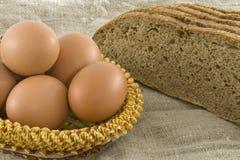 Ovos rurais que encontram-se em uma cesta perto do pão Imagem de Stock Royalty Free