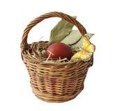 Ovos tingidos vermelhos e uma borboleta em uma cesta Imagens de Stock