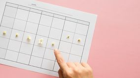 Ovulation cycle, concept. Calendar for a month, marker of ovulation and the menstrual cycle. On a pink background stock photography