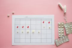 Ovulation cycle, concept. Calendar for a month, marker of ovulation and the menstrual cycle. Painkillers and birth control pills on a pink background stock images