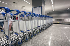 Ow of luggage trolleys at airport terminal Stock Image