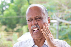 Ow tooth ache. Closeup portrait elderly business man with tooth ache crown problem cavity grimacing from pain touching outside mouth with hand isolated outside stock photography