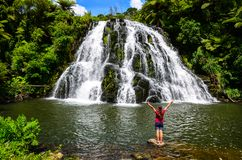 Free Owharoa Falls With Blue Sky Above And Girl Tourist Person In Red T-shirt In The Foreground At Coromandel Peninsula Stock Photos - 143973303