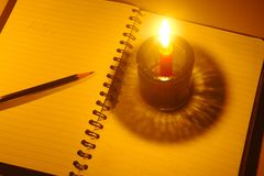 Ołówkowy stawiający na notatniku z świeczki światłem Obraz Stock