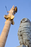 Owl And Athena. Close up of an owl,ancient symbol of wisdom, made of stone.At the background there is a statue of Athena,ancient goddess and patron of Athens Stock Photo