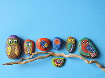 Owl and birds painted on stones. Colorful owl and birds painted on stone on wooden branch Stock Images