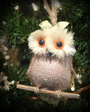 Owl Christmas Ornament. An owl Christmas tree ornament, perched on a twig, hanging on an evergreen Christmas tree with Christmas lights royalty free stock photo