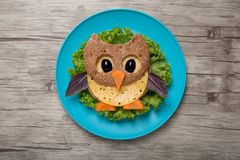 Owl made of bread and cheese. On plate and board stock image