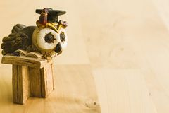 The owl professor. A miniature wooden owl dressed as a professor with a graduation hat. Read a book on the background of a brown wooden table. A small gift for a royalty free stock photo