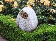 Owl sculpture in a Rose Garden Stock Image
