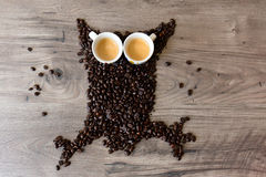 Owl shaped figure made out of coffee beans and two full espresso cups on top of a table Royalty Free Stock Image