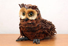 Owl straw decorative object on wooden shelf Royalty Free Stock Photo