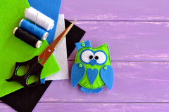 Owl toy is sewn from plush felt. Green fabric owl with blue heart and bow. Home decor idea for beginners and children Stock Photos