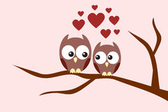 Owls couple in love. Sitting on a tree branch Stock Photo