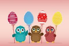 Owls keep Easter decorated eggs on a stick. Multicolored. Vector Royalty Free Stock Images