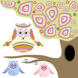 Owls. Three colorful abstract owl in a beautiful tree with a hollow Stock Photo
