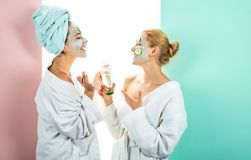Own spa salon at home. Conception of skin care by using white mask and cucumbers on the face. Two female sisters have stock image
