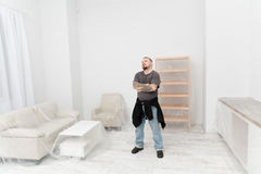 The owner of an apartment thinks how to rent it. Man standing in white room with furniture covered with foil royalty free stock photography