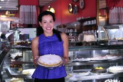 Owner of a cake store/ cafe. Owner of a small business store showing her tasty cakes stock photo