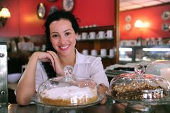 Owner of a cake store/ cafe. Owner of a small business store showing her tasty cakes royalty free stock image