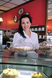 Owner of a cake store/ cafe. Owner of a small business/ cake store/ cafe showing her tasty cakes stock photography