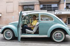 Owner of classic Volkswagen pale blue Beetle sitting in his car proudly holding golden trophy Stock Photography
