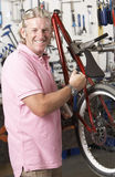 Owner of cycle shop in workshop. Looking happy stock photography