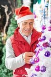 Owner Decorating Christmas Tree At Store Stock Images