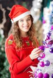 Owner Decorating Christmas Tree At Store Royalty Free Stock Image