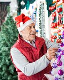 Owner Decorating Christmas Tree At Store Stock Photos