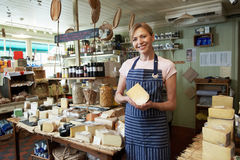 Owner Of Delicatessen Standing In Shop Holding Cheese. Owner Of Delicatessen Standing In Shop stock photography
