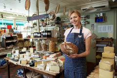 Owner Of Delicatessen Standing In Shop Holding Loaf Royalty Free Stock Image
