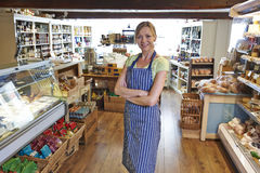 Owner Of Delicatessen Standing In Shop Royalty Free Stock Photo